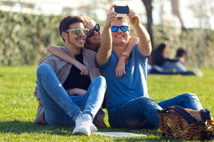 Group of students taking photos with a smartphone in the street. Royalty Free Stock Photo