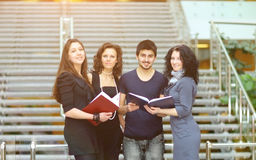 Group of students talking and holding notebooks Stock Image