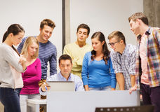 Group of students and teacher with laptop. Education, high school, technology and people concept - group of smiling students and teacher with papers, laptop Stock Images