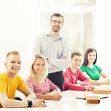 Group of students and a teacher at the lesson. Group of teenage students and a teacher at the lesson in the classroom. Education, school, college and university Royalty Free Stock Photo