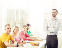Group of students and a teacher at the lesson. Group of teenage students and a teacher at the lesson in the classroom. Education, school, college and university Royalty Free Stock Images