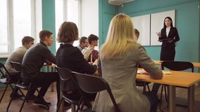 Students and a teacher woman during a lesson in a university class. Group of students and a teacher woman during a lesson in a university class stock video