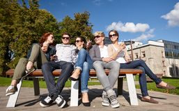 Group of students or teenagers drinking coffee. Summer holidays, friendship, leisure and teenage concept - group of happy students or teenagers hanging out and Stock Photo