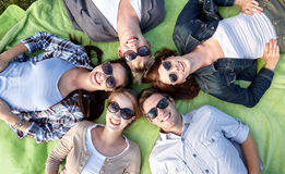 Group of students or teenagers lying in circle. Summer holidays, friendship, leisure and teenage concept - group of students or teenagers lying in circle at Royalty Free Stock Images