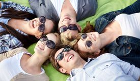 Group of students or teenagers lying in circle. Summer holidays, friendship, leisure and teenage concept - group of students or teenagers lying in circle at Stock Photos