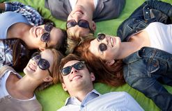 Group of students or teenagers lying in circle. Summer holidays, friendship, leisure and teenage concept - group of students or teenagers lying in circle at Royalty Free Stock Image