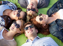 Group of students or teenagers lying in circle. Summer holidays, friendship, leisure and teenage concept - group of students or teenagers lying in circle at Royalty Free Stock Photography