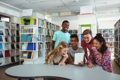 Group of students using digital tablet. At library Stock Photos
