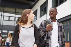 Group Of Students Walking Outside College Buildings stock photo
