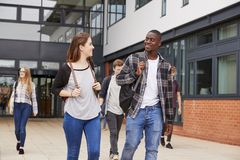 Group Of Students Walking Outside College Buildings royalty free stock photo