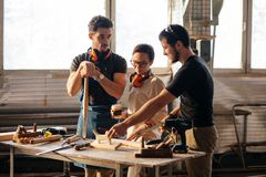 Carpenter Training Female Apprentice To Use Plane. Group of students in woodwork training course Stock Image