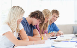 A group of students working as one student looks at the camera Royalty Free Stock Photo