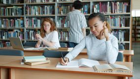 Group of students working in library reading books writing studying indoors