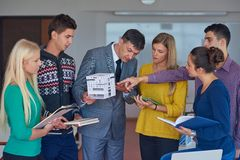 Group of students working with teacher on house model. Group of students working with teacher on wooden small house model royalty free stock photos
