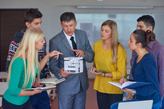 Group of students working with teacher on  house model Stock Image