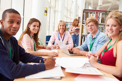 Group Of Students Working Together In Library With Teacher Stock Photography
