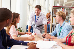 Group Of Students Working Together In Library With Teacher Stock Photos