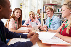 Group Of Students Working Together In Library With Teacher Royalty Free Stock Images