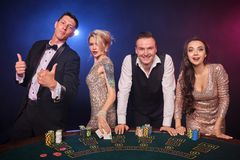 Group of a stylish rich friends are playing poker at casino. Group of a stylish rich classmates are playing poker at casino. Youth are making bets waiting for a stock image