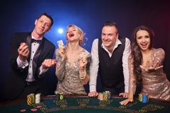 Group of a stylish rich friends are playing poker at casino. Group of a happy rich colleagues are playing poker at casino. Youth are making bets waiting for a royalty free stock photography