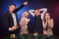 Group of a stylish rich friends are playing poker at casino. Group of a stylish rich companions are playing poker at casino. Youth are making bets waiting for a royalty free stock photo
