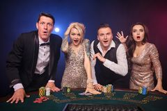 Group of a stylish rich friends are playing poker at casino. Group of a wondered rich classmates are playing poker at casino. Youth are making bets waiting for royalty free stock photo