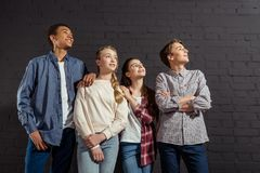 group of stylish teenagers standing together in front of black brick wall stock photos