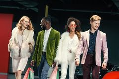 Group of stylish young multicultural shoppers walking. By auto showroom royalty free stock images