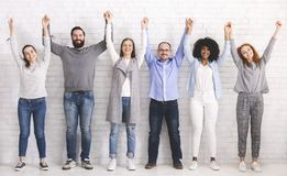 Group of successful friendly people raising connected hands stock images
