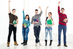 Group Of Successful Students With Books. Group of cheerful students with book's standing with arms raised in a fist in school hall and looking at camera Royalty Free Stock Photos
