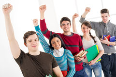 Group Of Successful Students. Group of cheerful students with book's standing In A Row with arms raised in a fist in school hall and looking at camera Royalty Free Stock Image