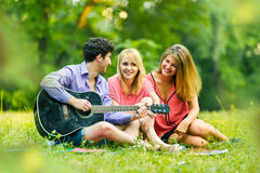 Group of successful students with a guitar resting Royalty Free Stock Photography
