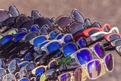 Group of sunglasses exposed in a market. Group of sunglasses exposed in a  outdoor market , with sun reflection on the lenses stock image