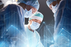 Group of surgeons in operating room at hospital. Surgery, healthcare, medicine and people concept - group of surgeons at operation in operating room at hospital Royalty Free Stock Photography