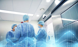 Group of surgeons in operating room at hospital. Surgery, medicine and people concept - group of surgeons in operating room at hospital talking and preparing to royalty free stock photography