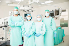 Group of surgeons in an OR. Portrait of a team of four surgeons standing in front of the operating room, ready to work on a patient Royalty Free Stock Image