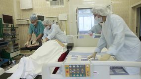 A group of surgeons shift the patient after surgery to a bed for transportation. Overall plan. A group of surgeons in surgical clothing shift the patient after stock video footage