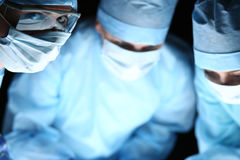 Group of surgeons at work operating in surgical theatre Stock Image