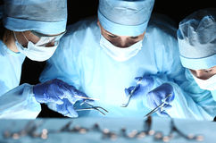 Group of surgeons at work operating in surgical theatre Royalty Free Stock Photos