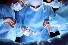 Group of surgeons at work in operating theater toned in blue Stock Photography
