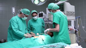 Group of surgeons working on an unconscious male patient stock video footage