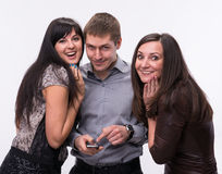 Group of surprised people looking at a cell phone Royalty Free Stock Photography