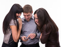 Group of surprised people looking at a cell phone Stock Photography