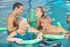 Group in swimming pool doing aqua. Happy group in swimming pool doing aqua fitness with swim noodles royalty free stock image