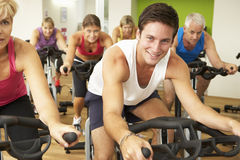 Group Taking Part In Spinning Class In Gym Stock Images