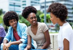 Group of talking african american young adults. Outdoor in the summer stock image