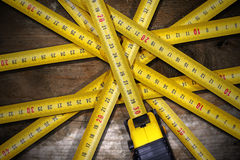 Group of Tape Measures on Wooden Table Stock Photography