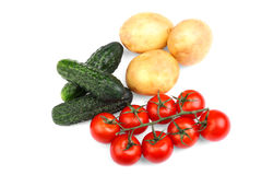 A group of tasteful red tomatoes, cucumbers, and potatoes,  on a white background. Healthful vegetables full of vitamins. Stock Images