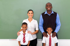 Group teachers students. Group of elementary school teachers and students in front of chalkboard stock image