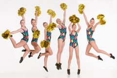 The group of teen cheerleaders jumping at white studio Stock Photos
